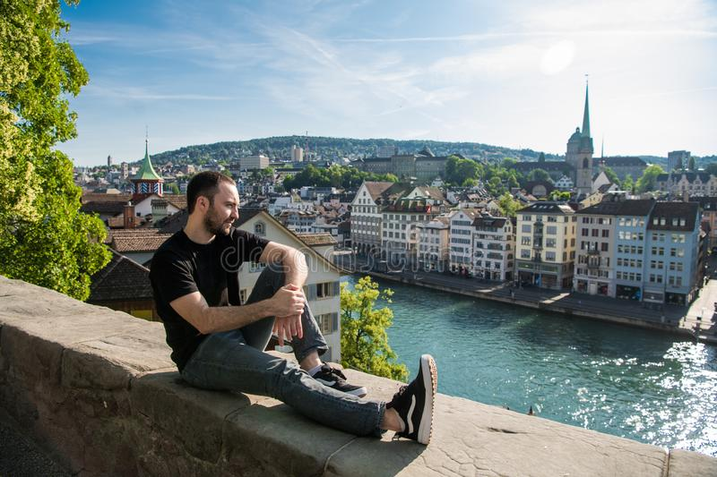 Handsome young guy sit in the city park with a city view in Zurich, Switzerland. royalty free stock image