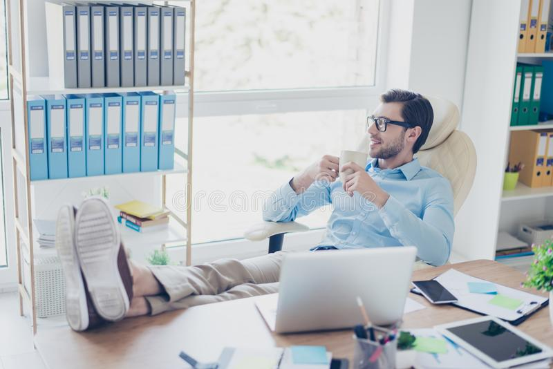 Handsome young happy worker in formal clothes and spectacles wit. H his feet on the table is having a long expected rest in his office after the serious stock images