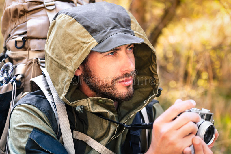 Handsome young hiker with camera stock image
