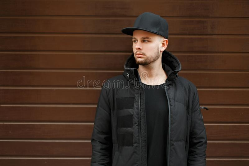 Handsome young hipster man in a black stylish baseball cap royalty free stock photography