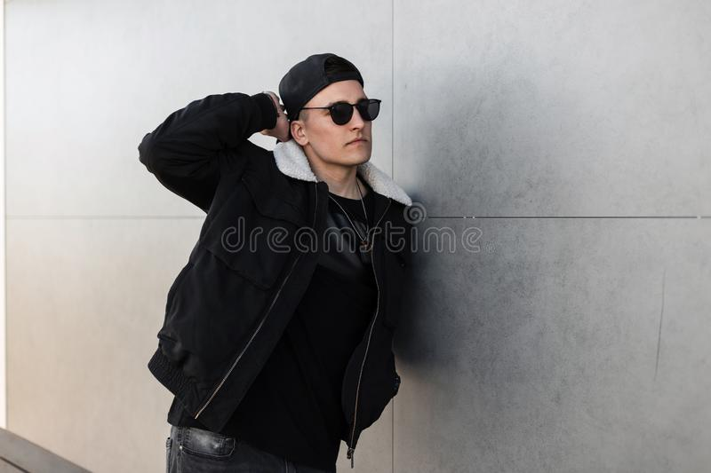 Handsome young hipster man in a fashionable jacket with white fur in sunglasses in a black stylish cap in a black T-shirt in jeans. Poses near a modern gray royalty free stock image