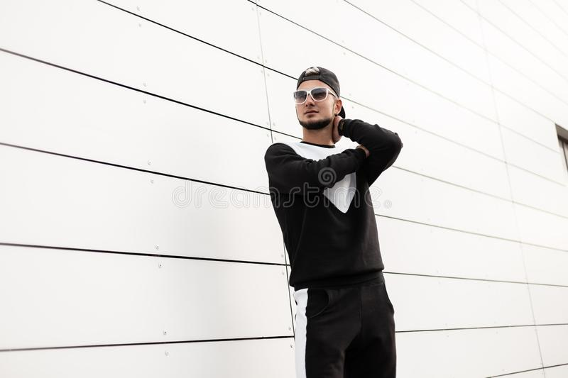 Handsome young hipster man in stylish baseball cap in trendy clothes in fashionable sunglasses is posing on a bright summer day. Near the white wall in the royalty free stock image