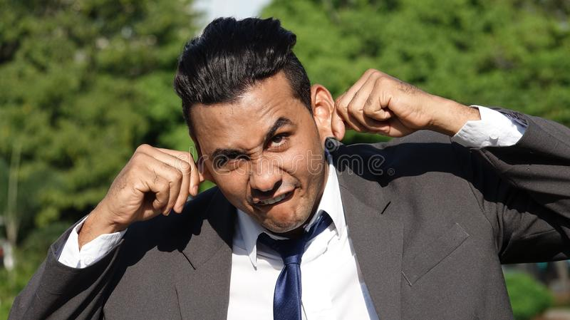 Business Man Making Funny Faces. A handsome young hispanic man stock image