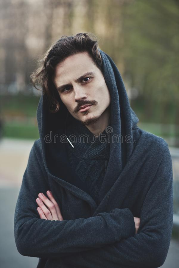 Handsome young hooded man looks on something with suspicion stock photo