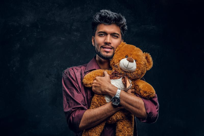 Handsome young Indian man in stylish shirt hugs teddy bear and looking at a camera. Studio photo against a dark textured wall royalty free stock image