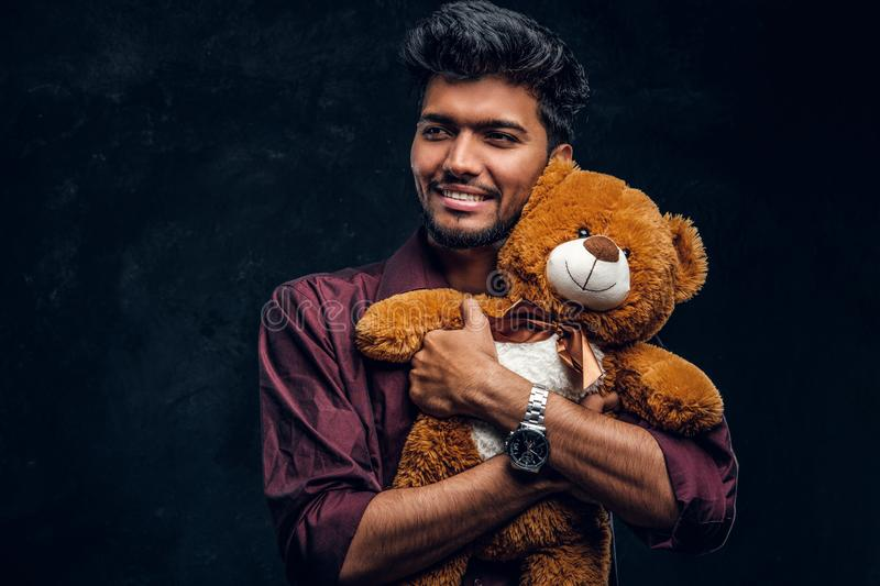 Handsome young Indian man in stylish shirt hugs teddy bear and looking sideways. Studio photo against a dark textured wall stock images