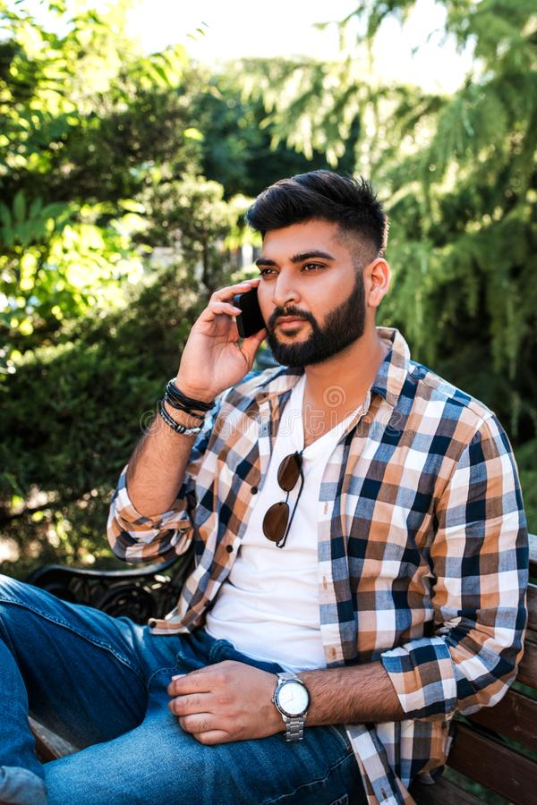Handsome young indian man using mobile phone. royalty free stock image