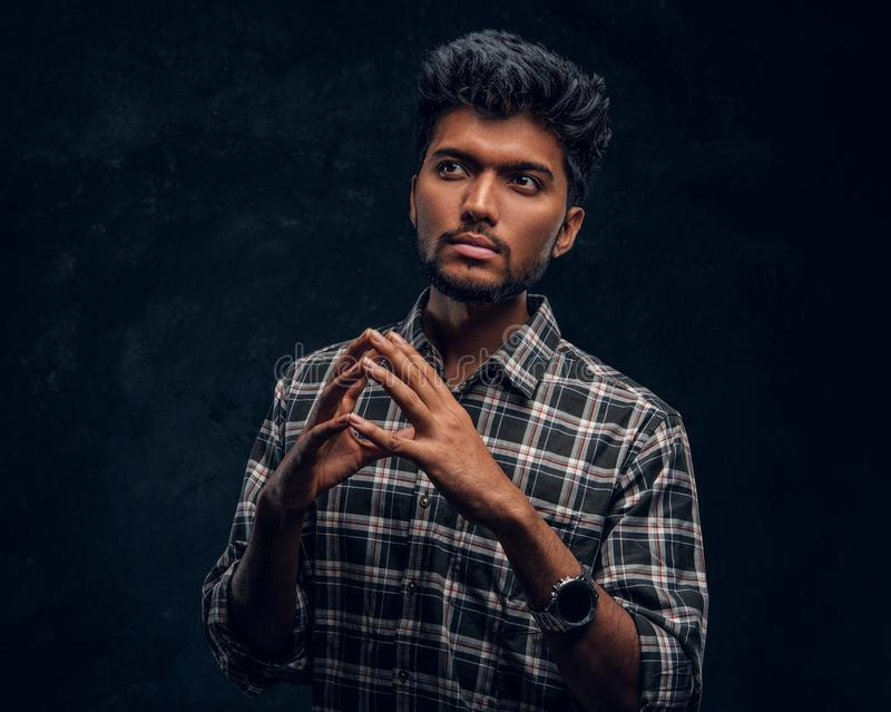 Handsome young Indian man wearing a checkered shirt posing for a camera and looking sideways. Studio photo against a dark textured wall stock photos