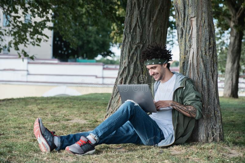 Handsome young international student sitting on grass in public park, typing text message on keyboard of modern laptop computer, royalty free stock photography