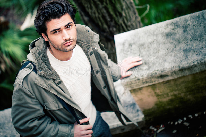 Handsome young italian man, stylish hair and coat outdoors royalty free stock photography