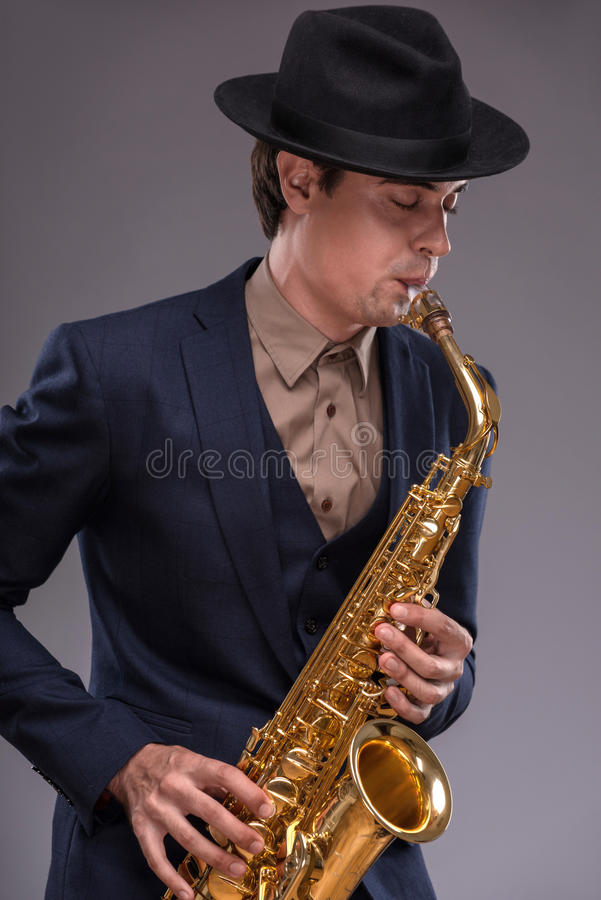 Handsome young jazz man. Waist-up portrait of a young handsome Caucasian jazz man in a suit with a black hat holding a trumpet in his hand and closing his eyes stock photos