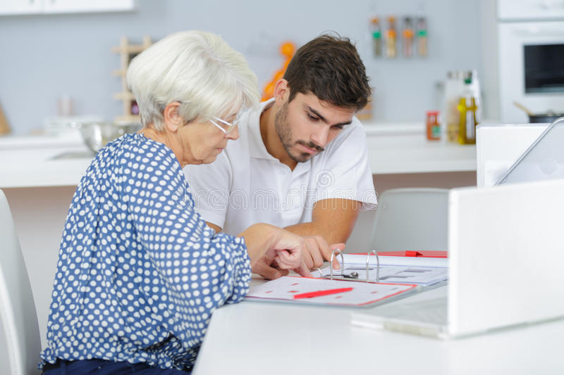 Handsome young lad helping senior lady with taxes royalty free stock photos