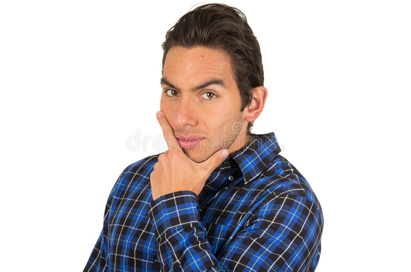 Handsome young latin man wearing a blue plaid. Handsome young flirty latin man wearing a blue plaid shirt posing with hand on chin isolated on white stock photo
