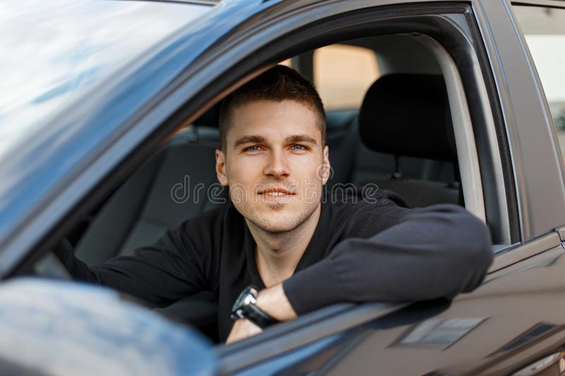Handsome young male driver in a black car. A handsome young male driver in a black car driving stock image