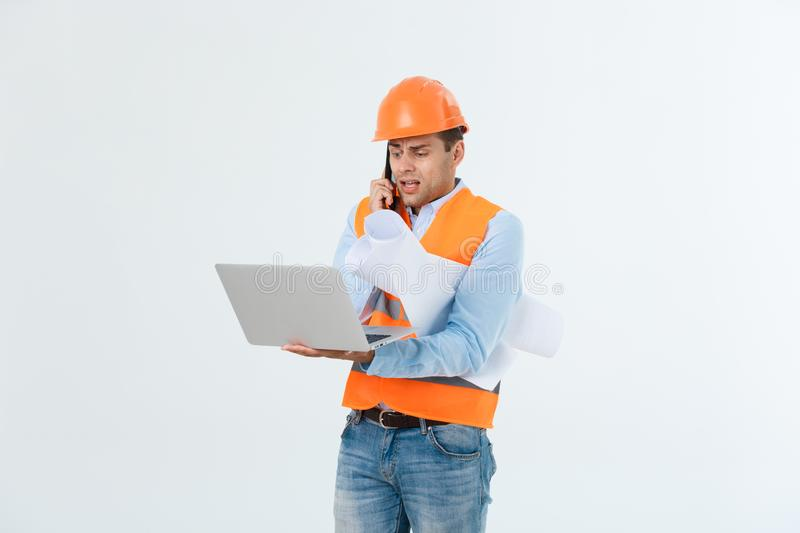 Handsome young male engineer with busy working on engineering project royalty free stock photography