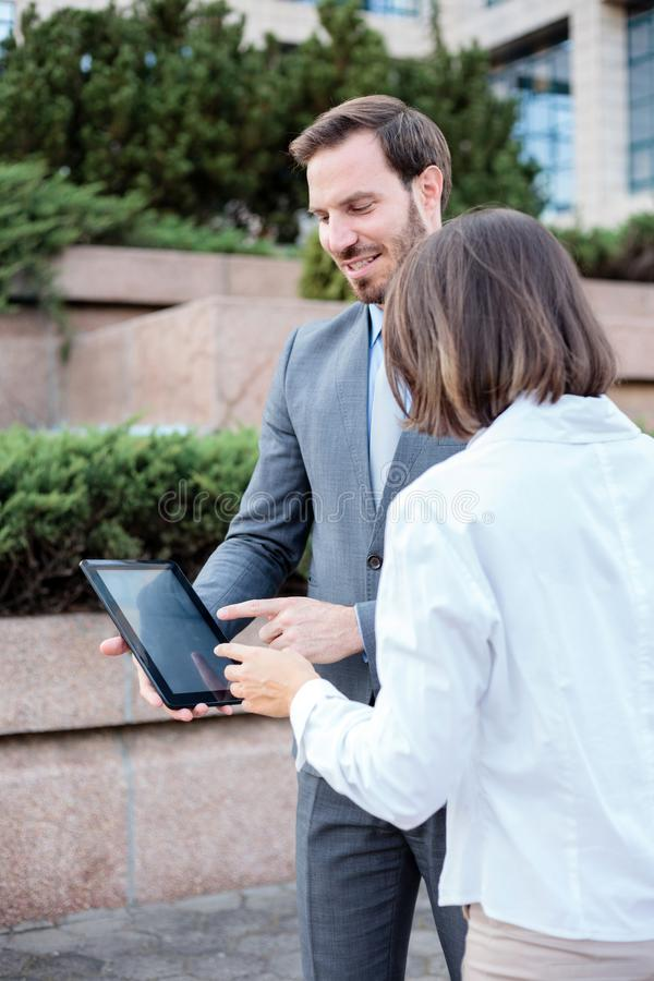 Handsome young male and female business people talking in front of an office building, having a meeting and discussing. Man is holding a tablet and pointing to royalty free stock photo
