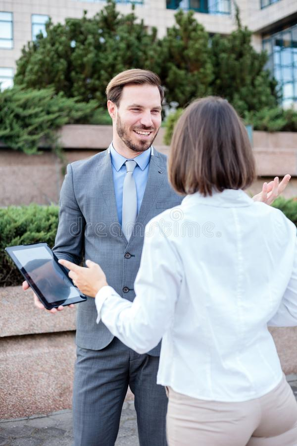 Handsome young male and female business people talking in front of an office building, having a meeting and discussing. Man is holding a tablet and looking at royalty free stock photography