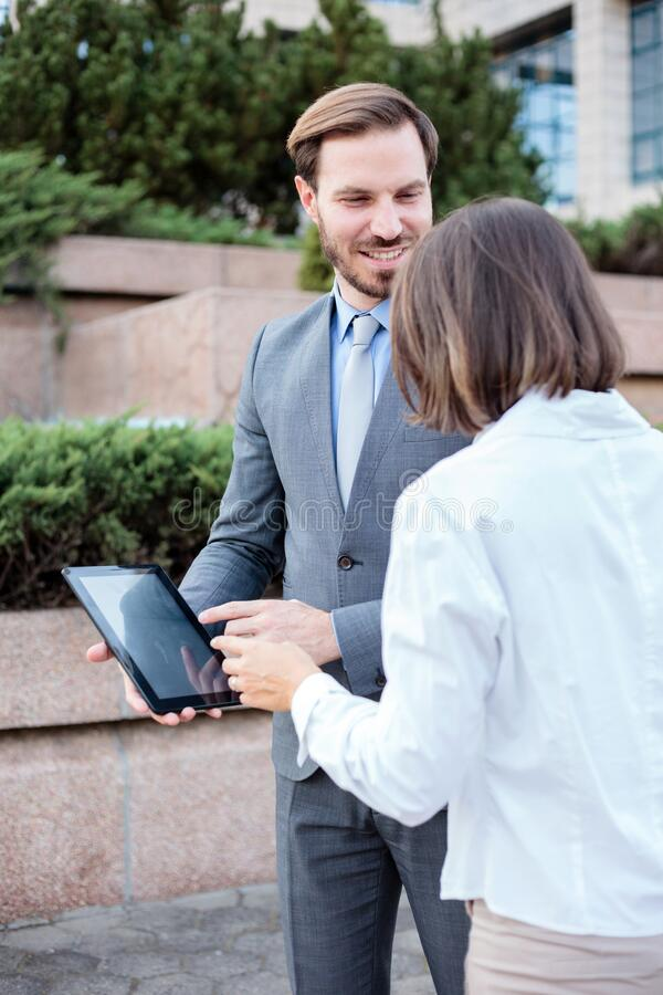 Handsome young male and female business people talking in front of an office building. Having a meeting and discussing. Man is holding a tablet and looking at royalty free stock images