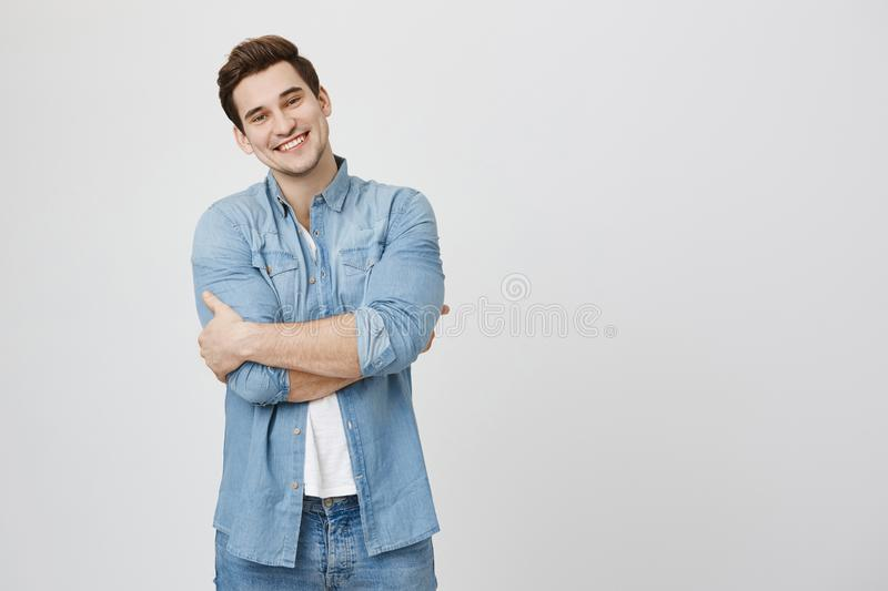 Handsome young male model with sincere happy smile and crossed hands looking at camera over white background, isolated royalty free stock photos