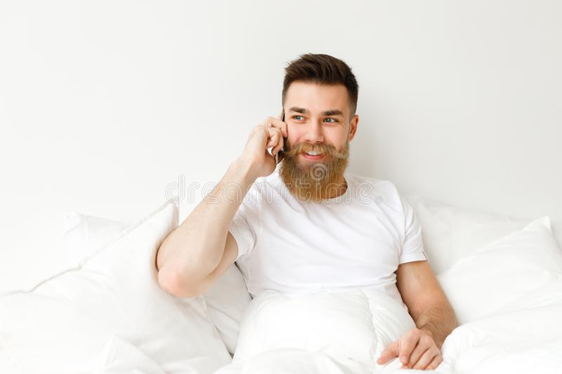 Handsome young male with thick beard and musttache dressed in casual clothes sits on comfortable bed, has conversation royalty free stock images