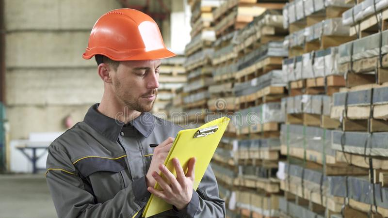 Warehouse worker writing on his clipboard standing at the storage stock images