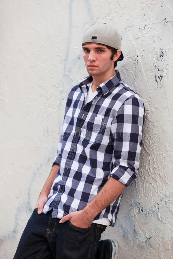 Handsome Young Man. In an urban fashion lifestyle pose leaning against a wall in a downtown alley and wearing a baseball cap royalty free stock image
