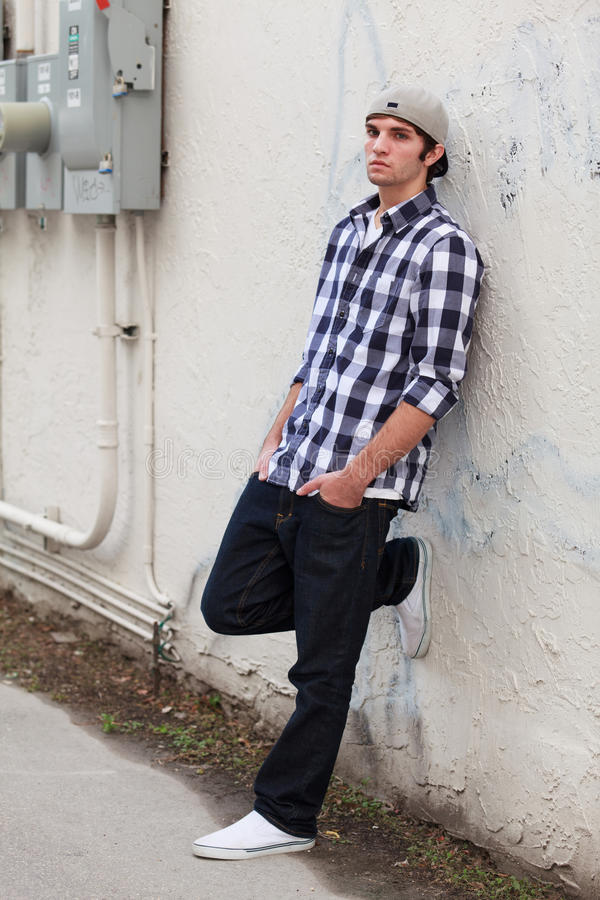 Handsome Young Man. In an urban fashion lifestyle pose in a alley downtown area and wearing a baseball cap stock photo