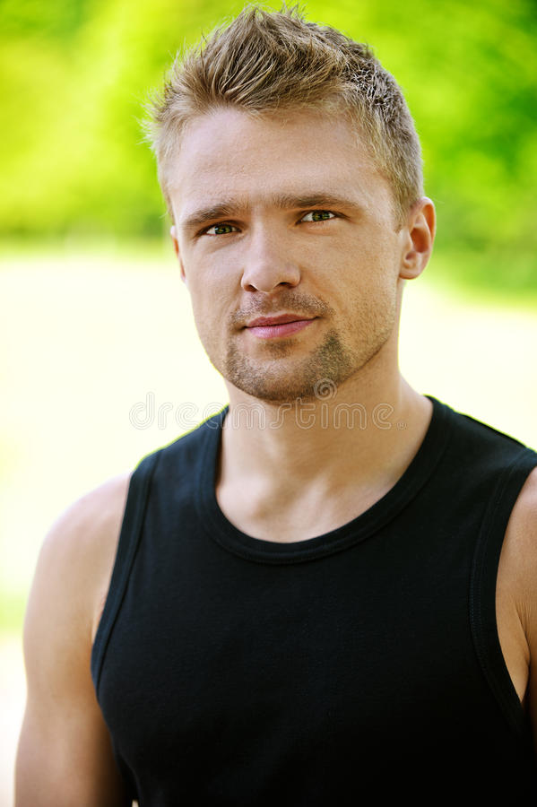 Handsome young man. Portrait of handsome young dressed in black man, against green of summer park royalty free stock images