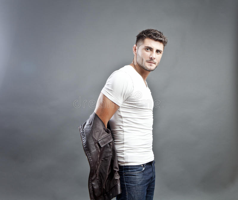 Handsome young man. On studio background taking off his leather jacket stock photo
