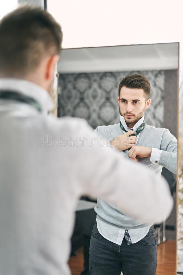 Handsome young man adjusting a tie in front of the mirror stock photography