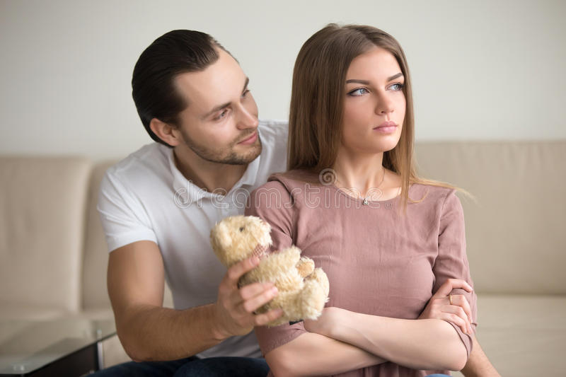 Handsome young man apologizing, presenting proud offended lady t. Guilty boyfriend asking for forgiveness, presenting offended girlfriend a teddy bear toy, lady stock images