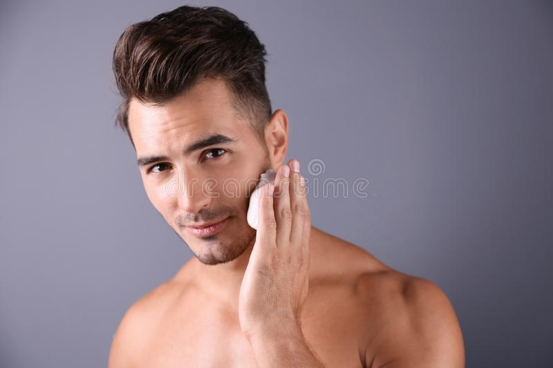 Handsome young man applying shaving foam royalty free stock photography