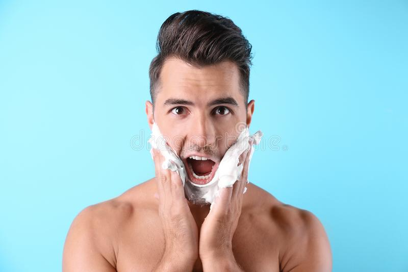 Handsome young man applying shaving foam. On color background stock photo