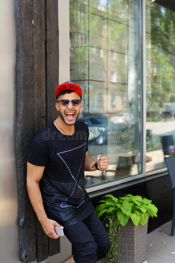 Handsome young man arab stands near wall smiles, rejoices and ho royalty free stock image