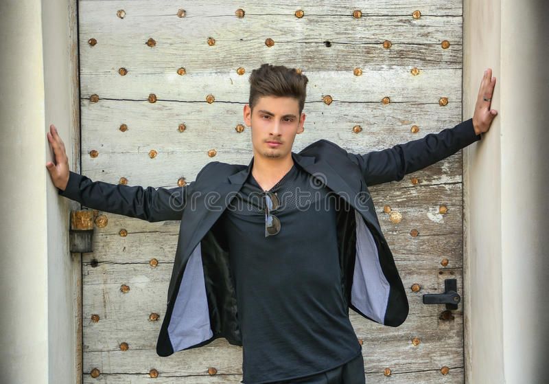 Handsome young man with arms spread open in front of old door royalty free stock photography