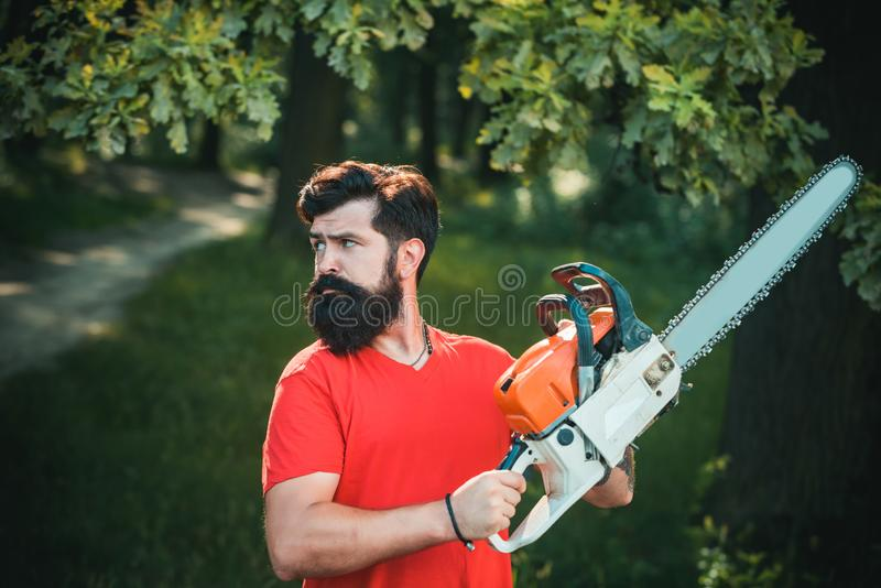 Handsome young man with axe near forest. Stylish young man posing like lumberjack. A handsome young man with a beard. Carries a tree stock photo