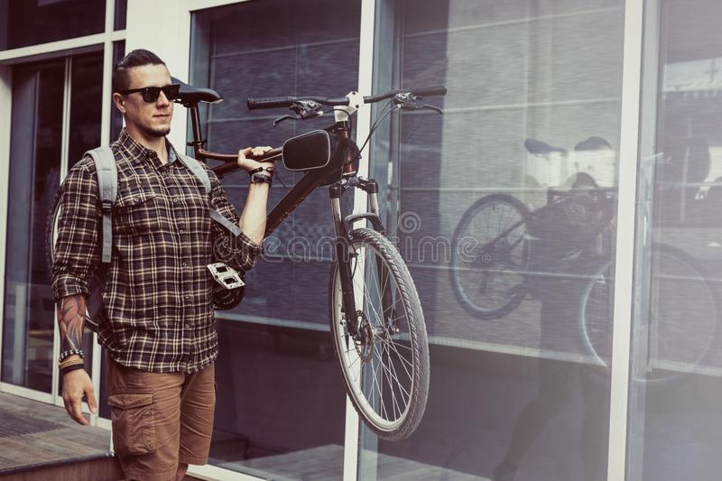 Handsome Young Man With Backpack Carries Bicycle On His Shoulder Livestyle Daily Routine Concept. Confident young handsome man with glasses carries a bicycle on stock photos