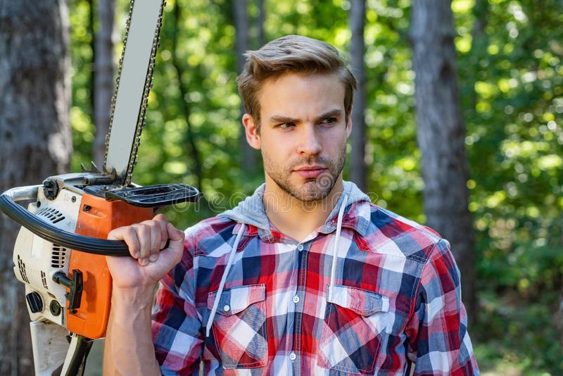 Handsome young man with a beard carries a tree. Woodworkers lumberjack. Firewood as a renewable energy source stock photos