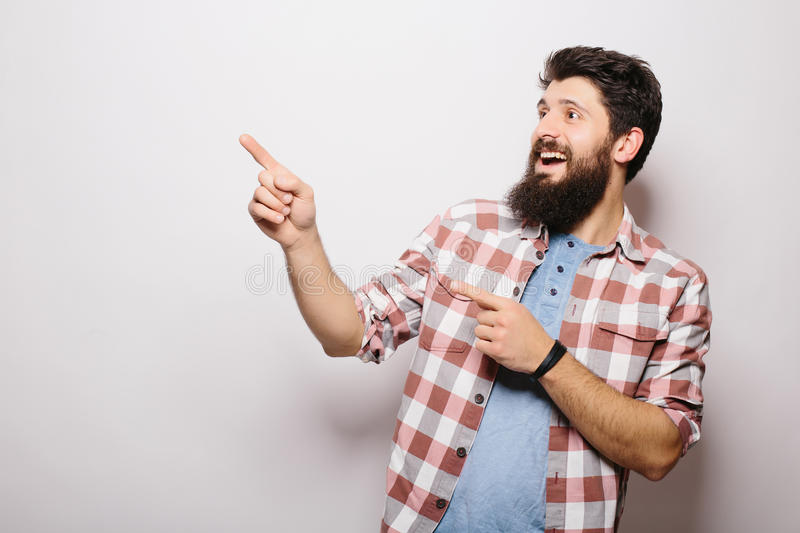 Handsome young man with beard demonstrate invisible product presentation or advertising pointed with hands. While standing against white background stock image