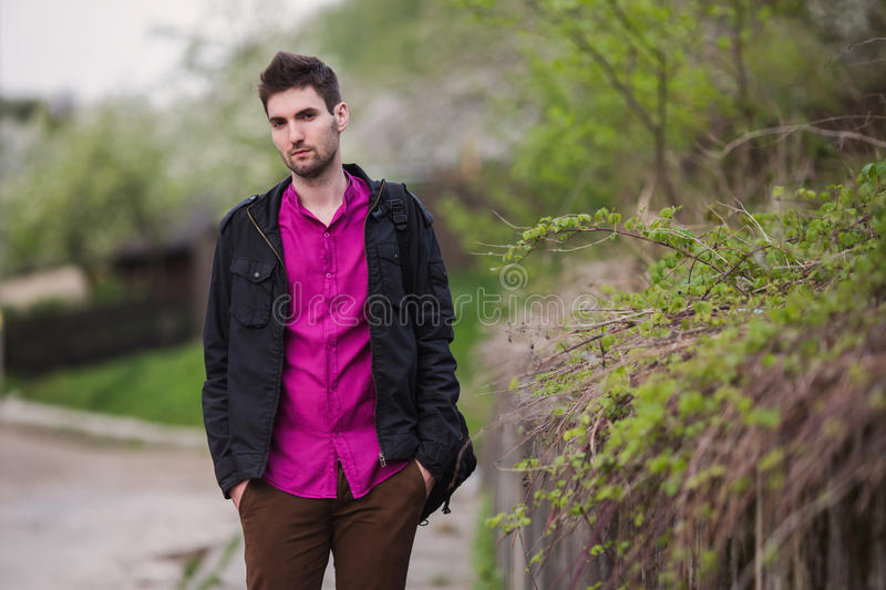 Handsome young man with a beard in a purple shirt and a black jacket on the street. Look at the camera, street style, put his hands in pocket, on a background stock photos