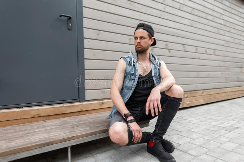 Handsome young man with a beard in a trendy denim vest in a T-shirt in stylish ripped jeans in sneakers in a vintage cap sits royalty free stock photos