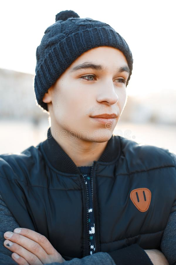 Handsome young man with beautiful blue eyes with tanned skin in a blue vintage knitted hat in a fashionable warm jacket. On the backdrop of a snowy city. Nice royalty free stock photography