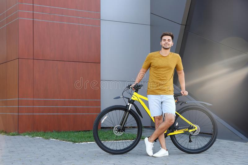 Handsome young man with bicycle on city street. Space  text stock images