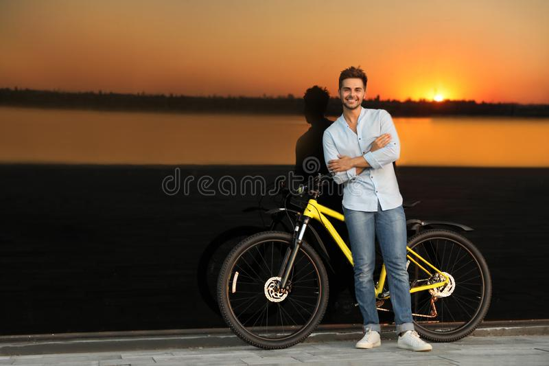 Handsome young man with bicycle near  building at sunset. Space for text royalty free stock image