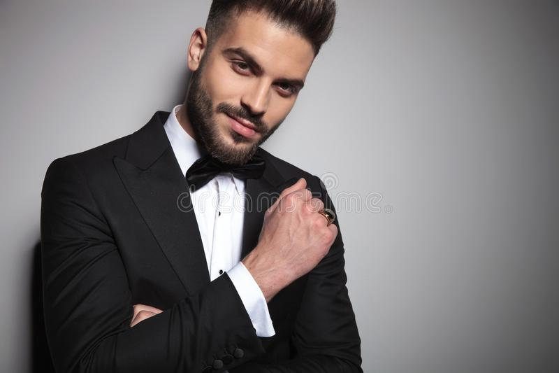 Handsome young man in black tuxedo holding arms folded royalty free stock photography