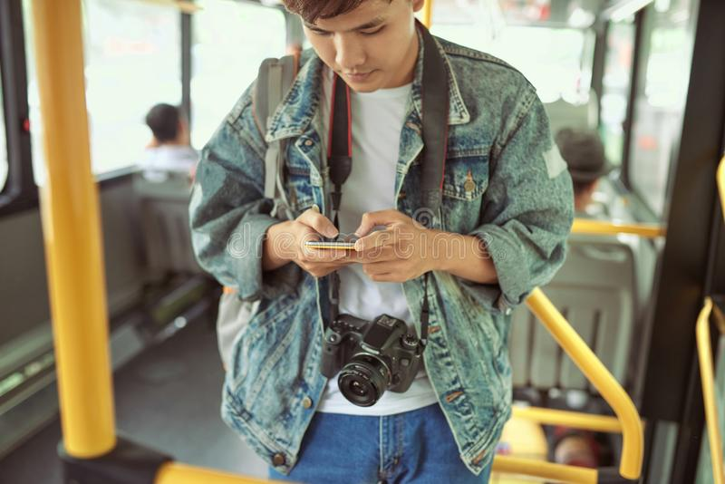Handsome young man in a blue denim jacket using smartphone in bu. S royalty free stock images