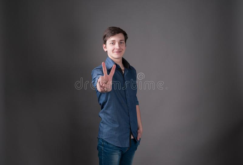 Handsome young man in blue looking at camera and showing peace sign with hand. On grey background with copy space royalty free stock image