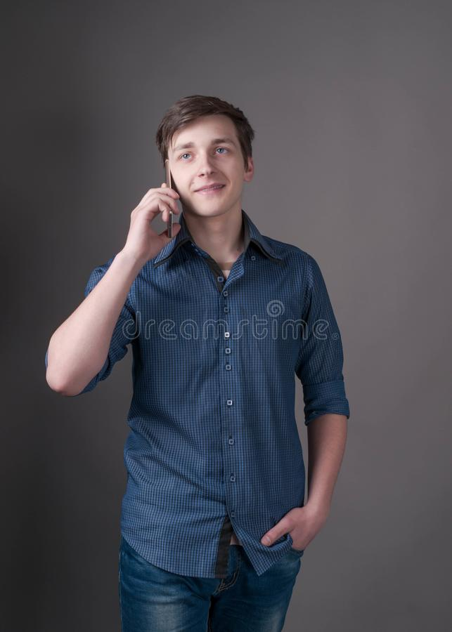 Handsome young man in blue shirt talking at smartphone and looking away on grey. Confident handsome young man in blue shirt talking at smartphone and looking stock photography