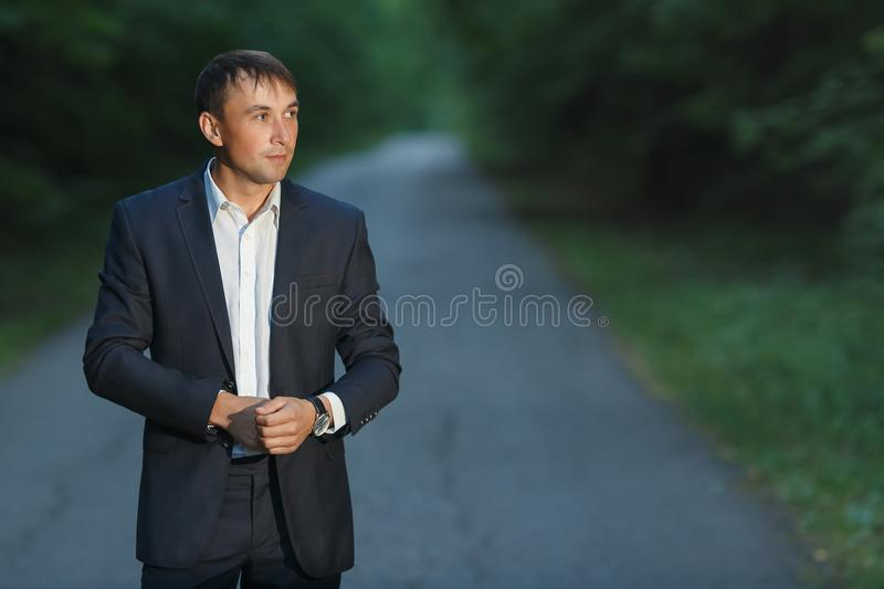 Handsome young man in a business suit walking on a forest road stock photo