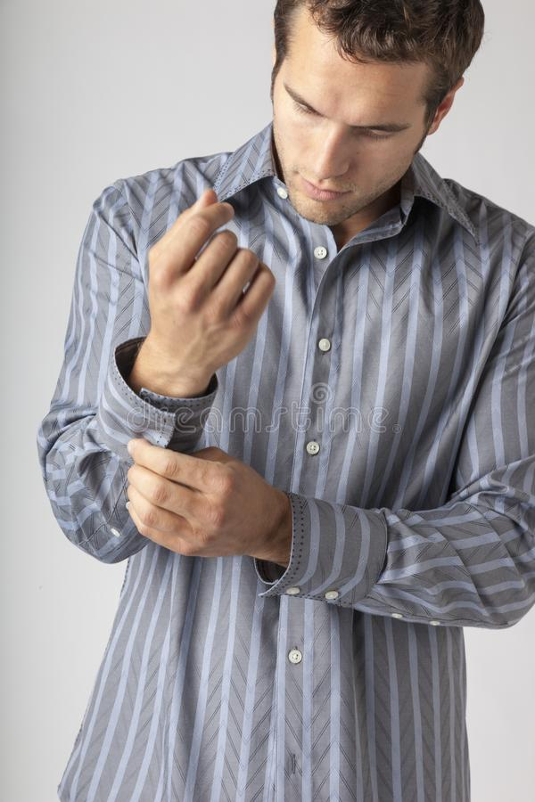 Handsome young man buttoning cuffs of dress shirt. Men`s clothing styles businessman getting ready for work putting on clean. Clothes stock photo